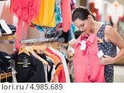 Купить «Девушка рассматривает новую блузку в магазине», фото № 4985689, снято 1 июня 2012 г. (c) Wavebreak Media / Фотобанк Лори