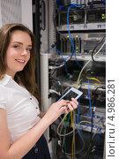 Купить «Улыбающаяся девушка с планшетным компьютером стоит около открытого щитка с проводами», фото № 4986281, снято 17 июля 2012 г. (c) Wavebreak Media / Фотобанк Лори