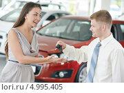 Купить «Продавец вручает женщине ключи от нового автомобиля», фото № 4995405, снято 18 мая 2013 г. (c) Дмитрий Калиновский / Фотобанк Лори