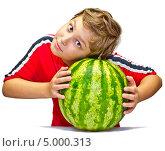 Мальчик проверяет арбуз на зрелость, сжимая его в руках. Стоковое фото, фотограф Дмитрий Морозов / Фотобанк Лори