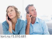 пожилая пара говорит по телефонам и смотрят в разные стороны. Стоковое фото, агентство Wavebreak Media / Фотобанк Лори