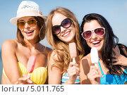 Веселые девушки наслаждаются мороженым на пляже жарким летним днем. Стоковое фото, фотограф Syda Productions / Фотобанк Лори