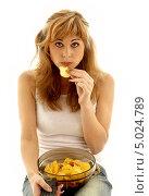 Девушка сидит на белом фоне и ест чипсы. Стоковое фото, фотограф Syda Productions / Фотобанк Лори