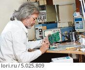 Купить «Инженер техник работает с микрочипом», фото № 5025809, снято 10 июля 2020 г. (c) Дмитрий Калиновский / Фотобанк Лори