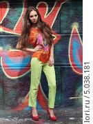 Красивая длинноволосая девушка на городской улице позирует на фоне стены, расписанной граффити (2013 год). Редакционное фото, фотограф Игорь Долгов / Фотобанк Лори
