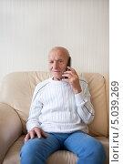 Купить «Пожилой улыбающийся мужчина разговаривает по телефону», фото № 5039269, снято 9 сентября 2013 г. (c) Victoria Demidova / Фотобанк Лори
