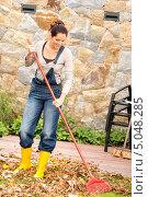 Купить «Девушка убирает опавшие листья», фото № 5048285, снято 23 сентября 2012 г. (c) CandyBox Images / Фотобанк Лори