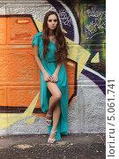 Купить «Длинноволосая девушка в голубом платье позирует на фоне стены, разрисованной краской», фото № 5061741, снято 8 июня 2013 г. (c) Игорь Долгов / Фотобанк Лори