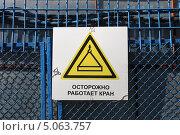 Купить «Предупреждающий желтый знак на металлическом заборе перед стройкой с надписью «Осторожно работает кран»», эксклюзивное фото № 5063757, снято 18 сентября 2013 г. (c) Алексей Гусев / Фотобанк Лори