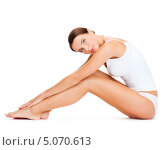 Купить «Красивая стройная брюнетка в скромном белом белье сидит на полу, согнув ноги в коленях», фото № 5070613, снято 25 июля 2013 г. (c) Syda Productions / Фотобанк Лори