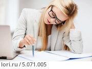 Купить «Деловая женщина работает с документами, сидя за рабочим столом», фото № 5071005, снято 30 марта 2013 г. (c) Syda Productions / Фотобанк Лори