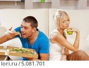 Купить «Счастливый молодой человек ест пиццу, а девушка - яблоко», фото № 5081701, снято 4 августа 2012 г. (c) Syda Productions / Фотобанк Лори