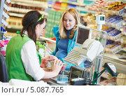Купить «Беременная женщина стоит у кассы супермаркета. Продавец пробивает покупки», фото № 5087765, снято 24 сентября 2013 г. (c) Дмитрий Калиновский / Фотобанк Лори