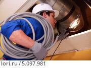Электрик с мотком кабеля занимается проводкой в здании. Стоковое фото, фотограф Phovoir Images / Фотобанк Лори