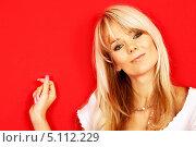 Купить «Энергичная блондинка на красном фоне», фото № 5112229, снято 7 октября 2006 г. (c) Syda Productions / Фотобанк Лори