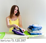 Купить «Молодая домохозяйка гладит свежее белье в комнате», фото № 5120397, снято 14 августа 2013 г. (c) Валерия Потапова / Фотобанк Лори