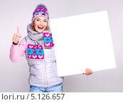 Купить «Молодая женщина в вязаной шапке держит в руке баннер и показывает большой палец вверх», фото № 5126657, снято 28 сентября 2013 г. (c) Валуа Виталий / Фотобанк Лори
