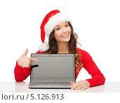 Купить «Счастливая девушка в шапке Санты Клауса сидит за столом с ноутбуком», фото № 5126913, снято 22 сентября 2013 г. (c) Syda Productions / Фотобанк Лори