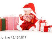 Купить «Маленький мальчик в шапке Санты Клауса с новогодними подарками», фото № 5134817, снято 13 сентября 2009 г. (c) Syda Productions / Фотобанк Лори