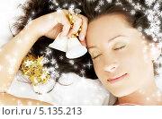 Счастливая девушка лежит на кровати с колокольчиком в руке. Стоковое фото, фотограф Syda Productions / Фотобанк Лори