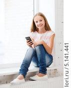 Счастливая девочка с мобильным телефоном сидит у окна в школе. Стоковое фото, фотограф Syda Productions / Фотобанк Лори