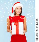 Купить «Счастливая девушка в шапке Санты с новогодними подарками на фоне снега», фото № 5141545, снято 15 августа 2013 г. (c) Syda Productions / Фотобанк Лори
