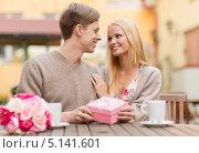 Купить «Романтическая пара с подарком за столиком кафе», фото № 5141601, снято 6 сентября 2013 г. (c) Syda Productions / Фотобанк Лори