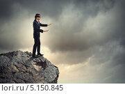 Купить «Бизнесмен с повязкой на глазах стоит, вытянув руки, на краю скалы над обрывом», фото № 5150845, снято 11 мая 2012 г. (c) Sergey Nivens / Фотобанк Лори