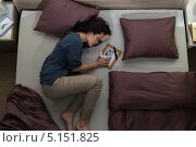 Несчастная женщина лежит на кровати и вспоминает, умершего мужа. Стоковое фото, фотограф CandyBox Images / Фотобанк Лори