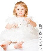 Купить «Маленькая светловолосая девочка в белом платье с сердитым выражением лица, с конфетой в руках, на белом фоне», фото № 5154829, снято 13 декабря 2009 г. (c) Станислав Фридкин / Фотобанк Лори