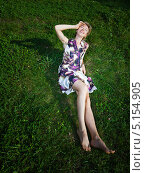 Купить «Веселая босая молодая женщина сидит на зеленой траве и смотрит наверх», фото № 5154905, снято 3 сентября 2009 г. (c) Станислав Фридкин / Фотобанк Лори