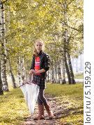 Купить «Девочка с зонтиком стоит в осеннем парке», фото № 5159229, снято 7 сентября 2013 г. (c) Гурьянов Андрей / Фотобанк Лори