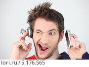 Парень слушает одним ухом наушник, а другим сотовый телефон. Стоковое фото, фотограф Phovoir Images / Фотобанк Лори