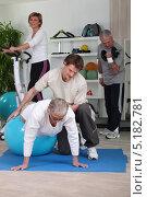 Купить «Пожилая женщина занимается в спортзале с тренером», фото № 5182781, снято 13 апреля 2010 г. (c) Phovoir Images / Фотобанк Лори