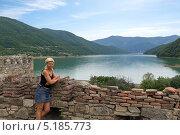 Купить «Молодая женщина у крепостной стены на фоне горного озера», фото № 5185773, снято 2 июля 2013 г. (c) Евгений Ткачёв / Фотобанк Лори