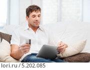 Купить «Мужчина с кредитной картой и планшетным компьютером в гостиной», фото № 5202085, снято 3 октября 2013 г. (c) Syda Productions / Фотобанк Лори