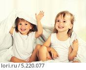 Счастливые сестры-близнецы играют под одеялом. Стоковое фото, фотограф Евгений Атаманенко / Фотобанк Лори