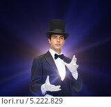 Купить «Молодой фокусник в смокинге показывает магический трюк», фото № 5222829, снято 12 сентября 2013 г. (c) Syda Productions / Фотобанк Лори