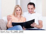 Купить «радостные мужчина и женщина сидят на диване и смотрят фотоальбом», фото № 5240289, снято 19 мая 2013 г. (c) Андрей Попов / Фотобанк Лори