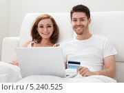 Купить «молодая пара совершает покупки, лежа с ноутбуком в кровати», фото № 5240525, снято 21 апреля 2013 г. (c) Андрей Попов / Фотобанк Лори