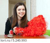 Купить «Девушка сидит за столом с красным париком», фото № 5240993, снято 21 декабря 2012 г. (c) Яков Филимонов / Фотобанк Лори