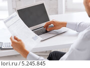 Купить «Бизнесмен в голубой сорочке работает с бумагами за столом в офисе», фото № 5245845, снято 9 июня 2013 г. (c) Syda Productions / Фотобанк Лори