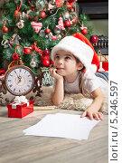 Купить «Маленькая девочка в красном колпаке около елки мечтает о новогоднем подарке», фото № 5246597, снято 2 ноября 2013 г. (c) Оксана Гильман / Фотобанк Лори