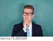 Купить «молодой мужчина в очках и деловом костюме о чем-то размышляет», фото № 5250029, снято 6 июля 2013 г. (c) Андрей Попов / Фотобанк Лори