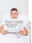 Купить «молодой мужчина читает утреннюю газету, лежа в постели», фото № 5250137, снято 6 июля 2013 г. (c) Андрей Попов / Фотобанк Лори