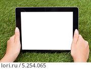 Купить «женские руки держат цифровой планшет с пустым экраном на фоне зеленой травы», фото № 5254065, снято 14 августа 2013 г. (c) Андрей Попов / Фотобанк Лори