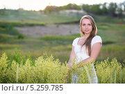 Купить «Улыбающаяся блондинка стоит в летнем поле», фото № 5259785, снято 2 июня 2013 г. (c) Сергей Сухоруков / Фотобанк Лори