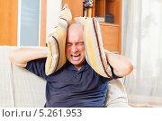 Купить «Мужчина закрывает уши подушками», фото № 5261953, снято 18 октября 2013 г. (c) Дарья Филимонова / Фотобанк Лори