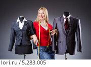 Портниха стоит между двух манекенов с готовыми мужским и женским деловыми костюмами. Стоковое фото, фотограф Elnur / Фотобанк Лори