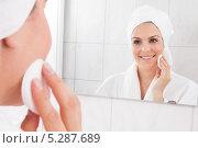 Купить «Красивая женщина протирает лицо, стоя у зеркала», фото № 5287689, снято 16 июня 2013 г. (c) Андрей Попов / Фотобанк Лори